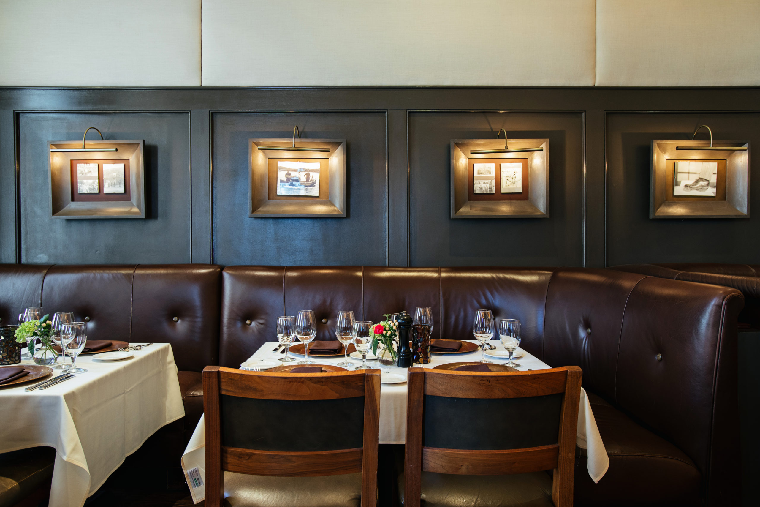 Elegant dinner table with table linens, leather booth seating and a feature wall of artwork lit by overhead lamps