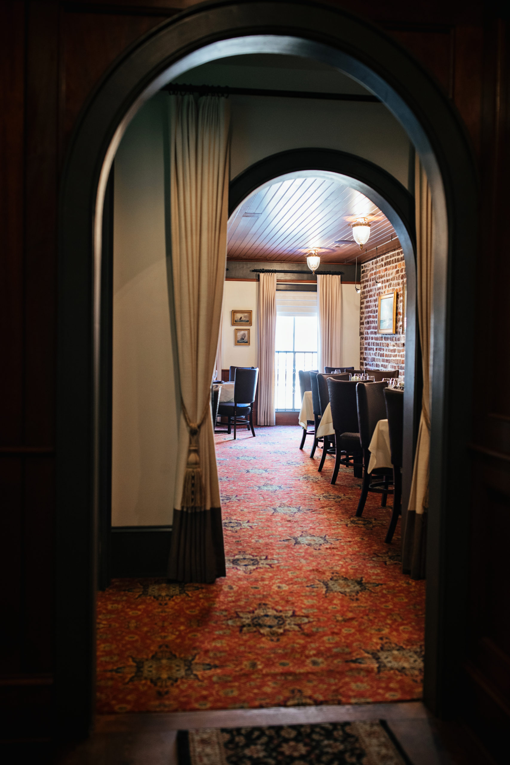Arched hallway leaving to a restaurant dining room with exposed brick wall