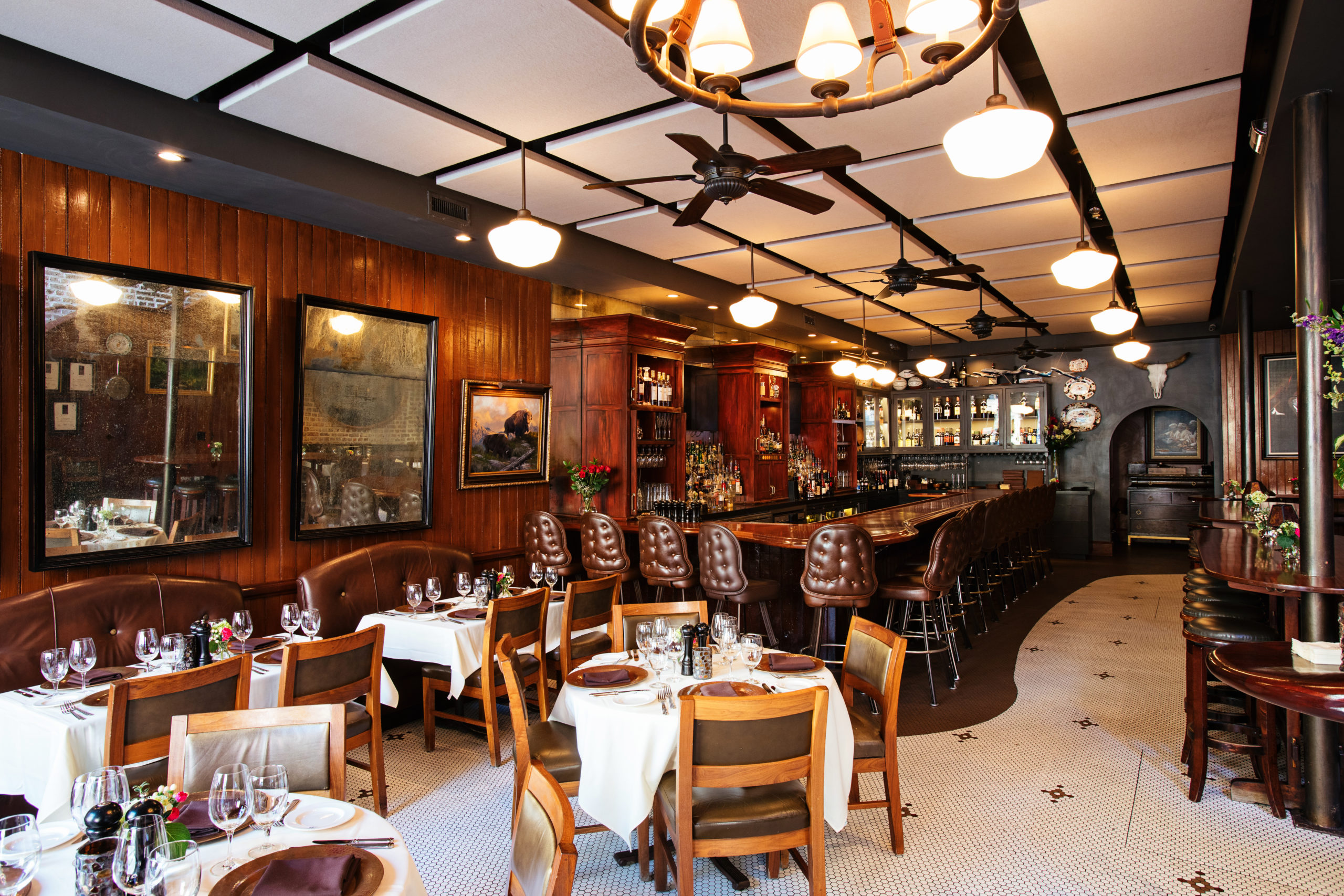 restaurant bar with leather bar stools, dark wood paneling, and intimate dining tables with elegant table settings